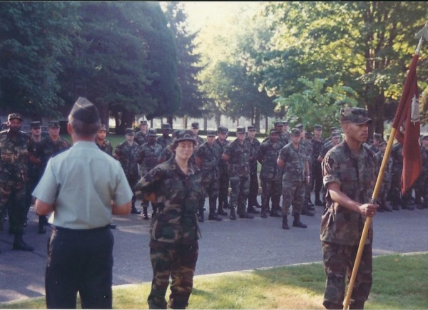 Me standing in front of formation with an officer to the left and the soldier with the guidon on the right.