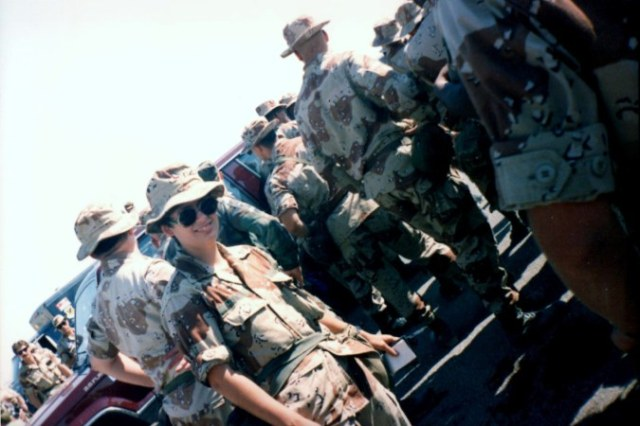 Linda Adams poses for camera in desert combat uniform