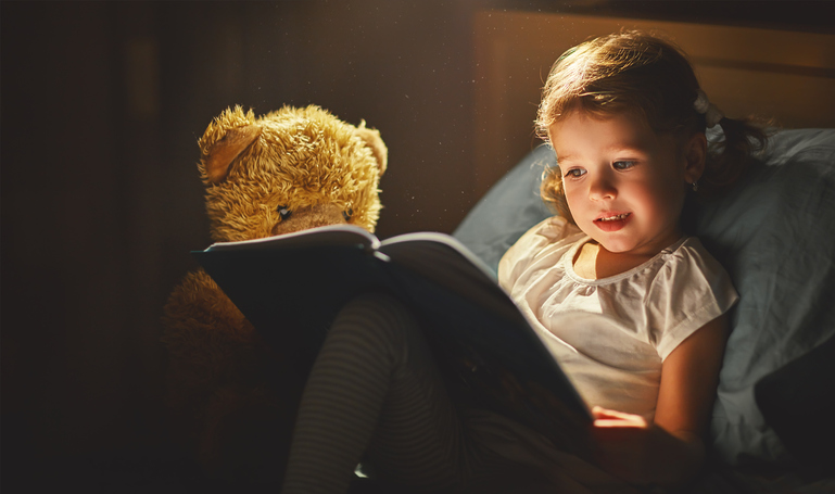 Learning about reading: A little girl sits next to her teddy bear and excitedly reads a book