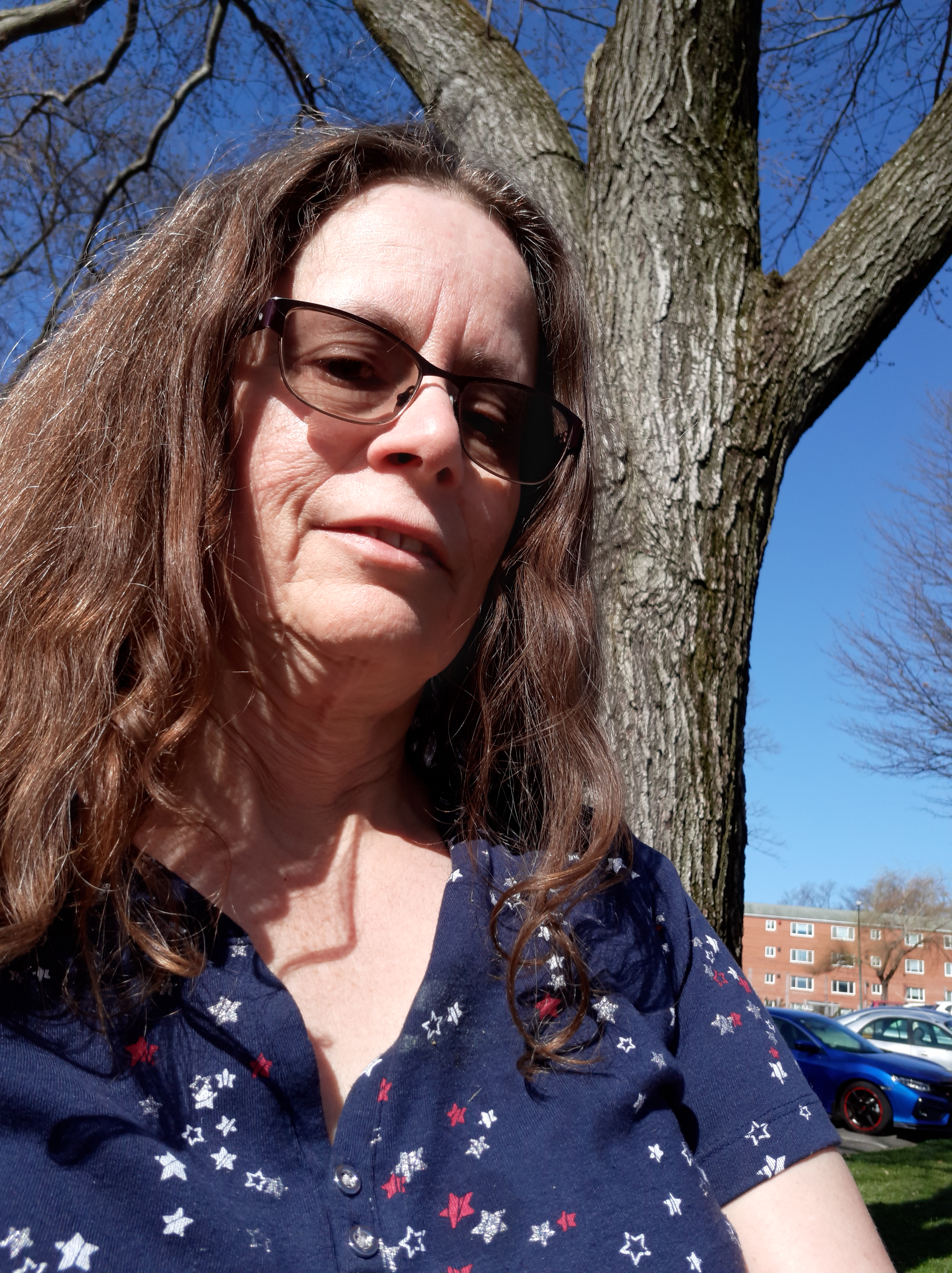 Writer Linda Maye Adams out by a tree on a spring day
