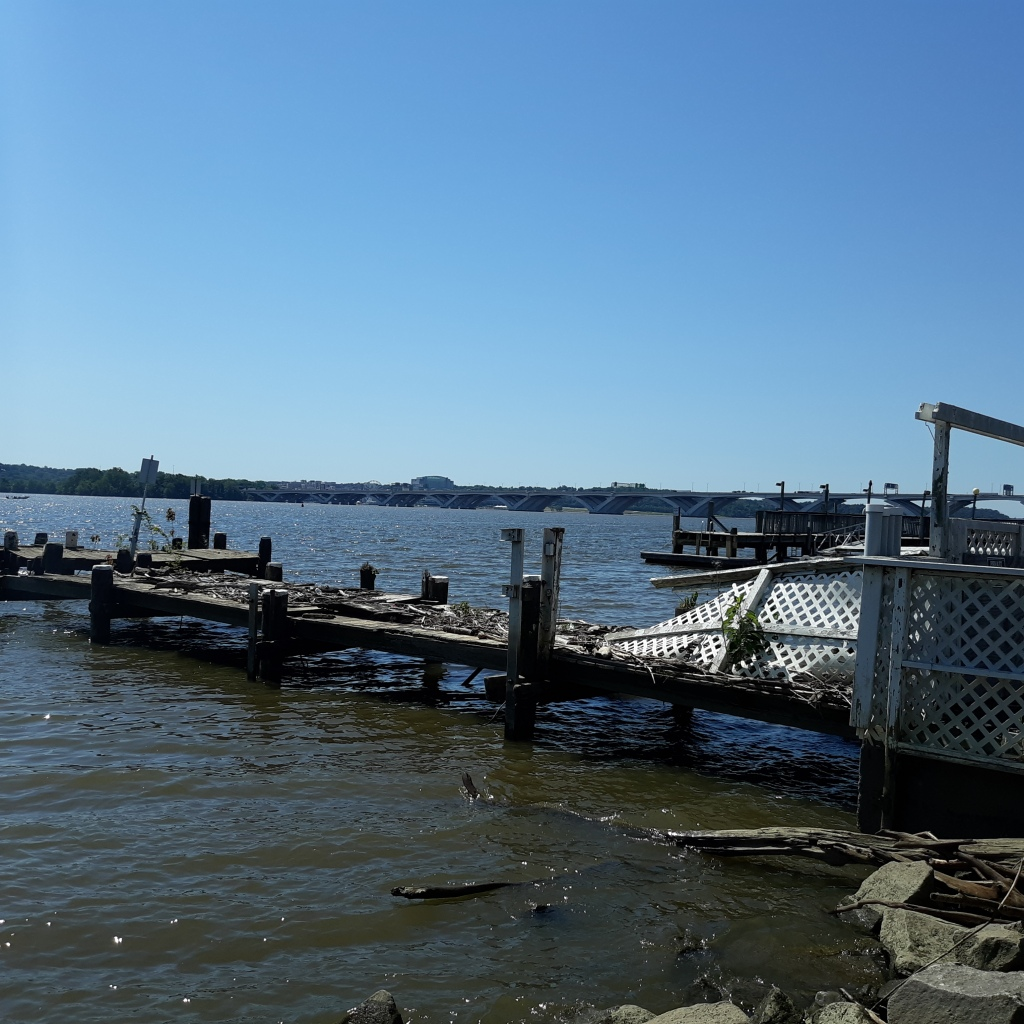 A private dock, partially broken up by storms and covered with debris.