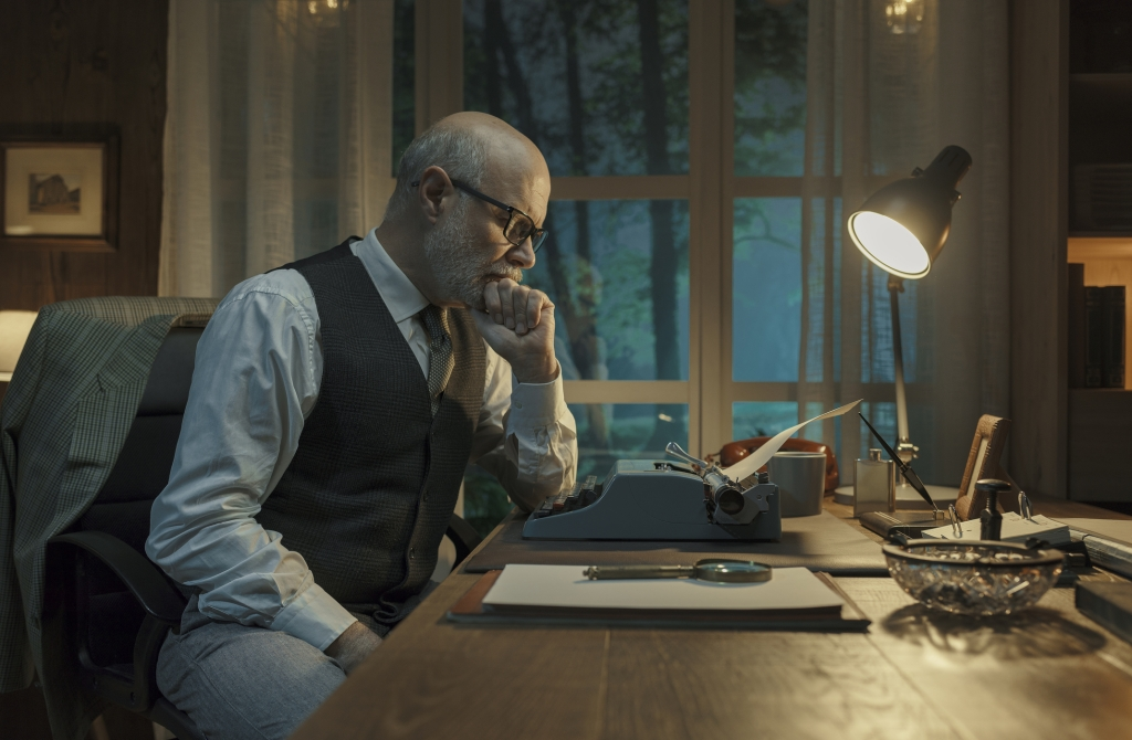 A man in an old-time vest stares thoughtfully down at his manual typwriter.